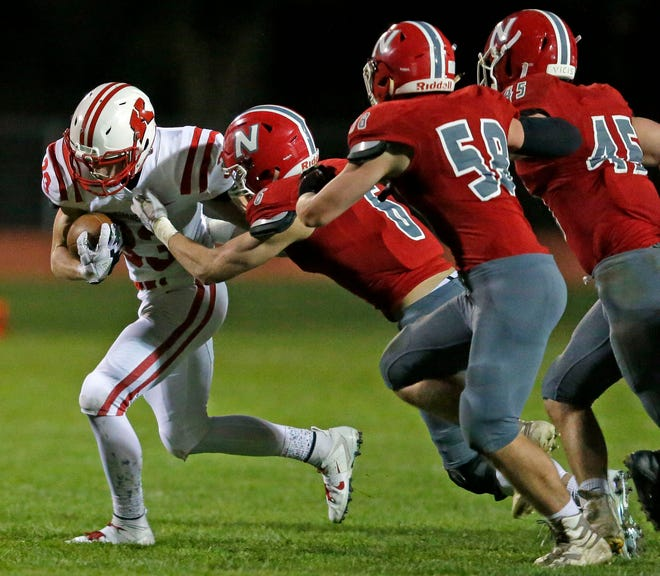 Caleb Frazer of Kimberly is pursued by Ethan Parker, Kaiden Sell and Reid Koeppel of Neenah in a Valley Football Association game Friday. Kimberly moved up to No. 3 in the latest AP state high school football poll after a shutout win. Neenah dropped out of the top 10.