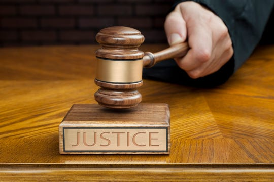 """Judge's Hand Pounding Gavel To End Courtroom Trial. Selective focus is on Gavel and Block with the singular word """"JUSTICE""""."""
