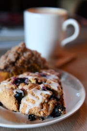 A latte is accompanied by a vegan scone and house-made pumpkin chocolate chip coffee cake at the Beehive Coffee Bar in Arden.