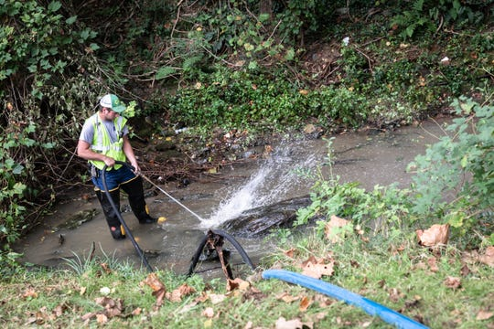 Gray Clough, a worker with Buncombe County's Metropolitan Sewage District uses a hose to push solid waste downstream off of South French Broad Ave. Sept. 24, 2018, after a sewage spill Friday.