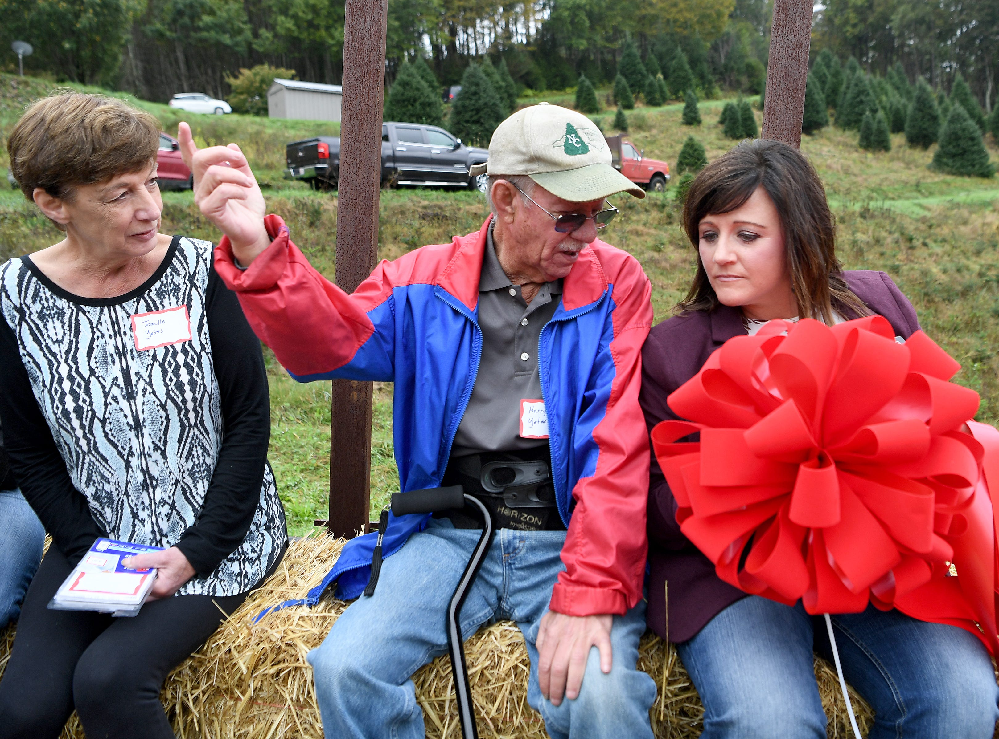Janelle and Harry Yates talk with Jennifer Greene, executive director of the North Carolina Christmas Tree Association, as they are led through Mountain Top Fraser Fir, a Christmas tree farm in Newland, to watch White House officials pick out a tree for the Blue Room of the White House.