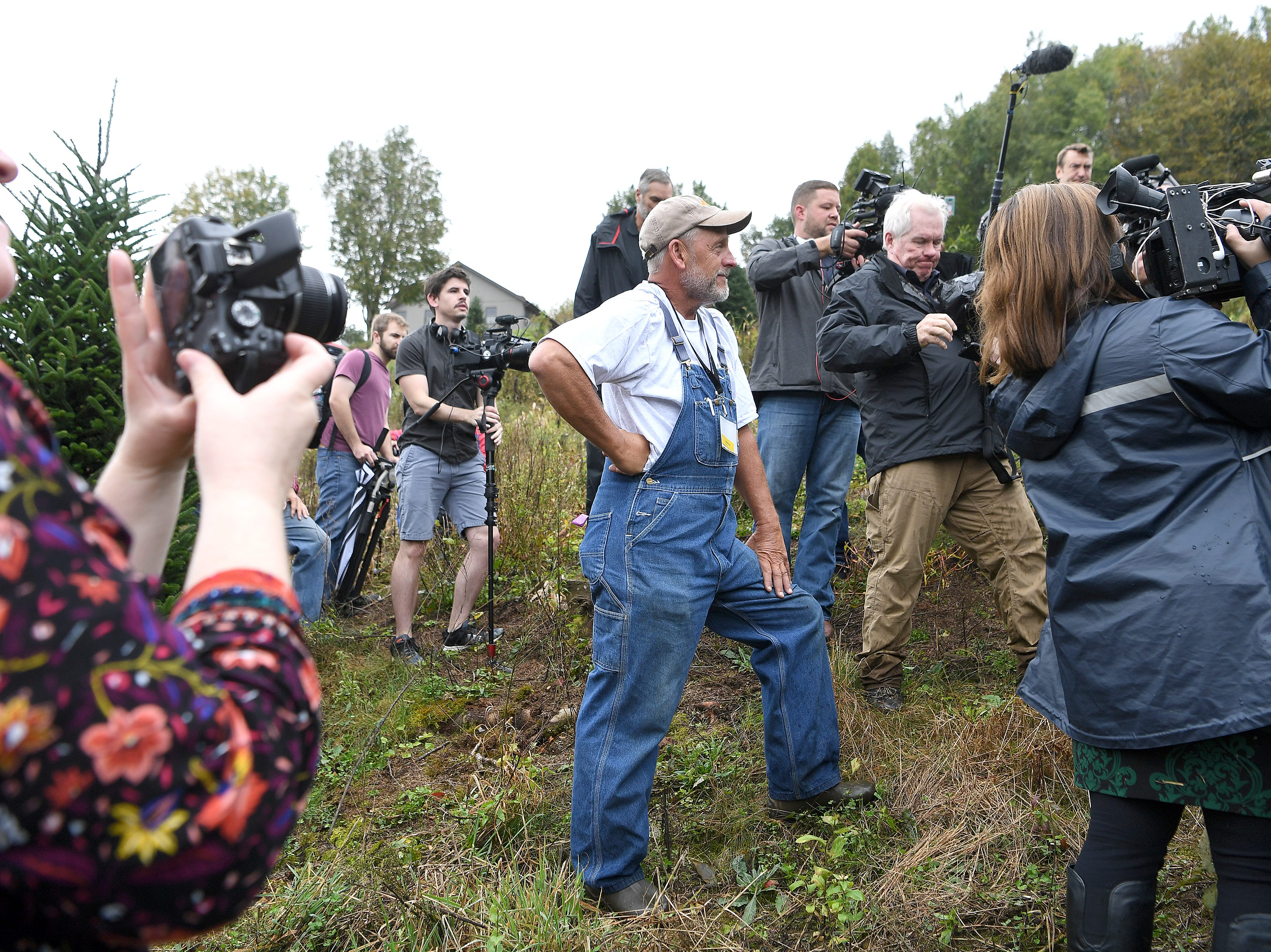 Avery County Christmas tree grower Larry Smith watches as White House officials are recorded by member of the media as they search his farm for the perfect tree to display in the Blue Room of the White House during an event at his farm in Newland on Sept. 24, 2018. Smith was given the honor of providing a tree after being named Grand Champion in the National Christmas Tree Association's Christmas tree contest.