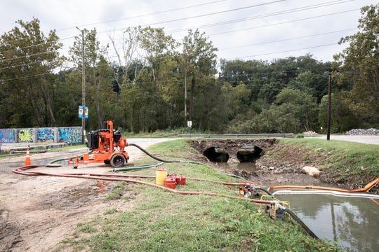 A pump on Lyman Street removes solid waste from a creek feeding into the French Broad River Sept. 24, 2018, after a sewage spill on Friday.
