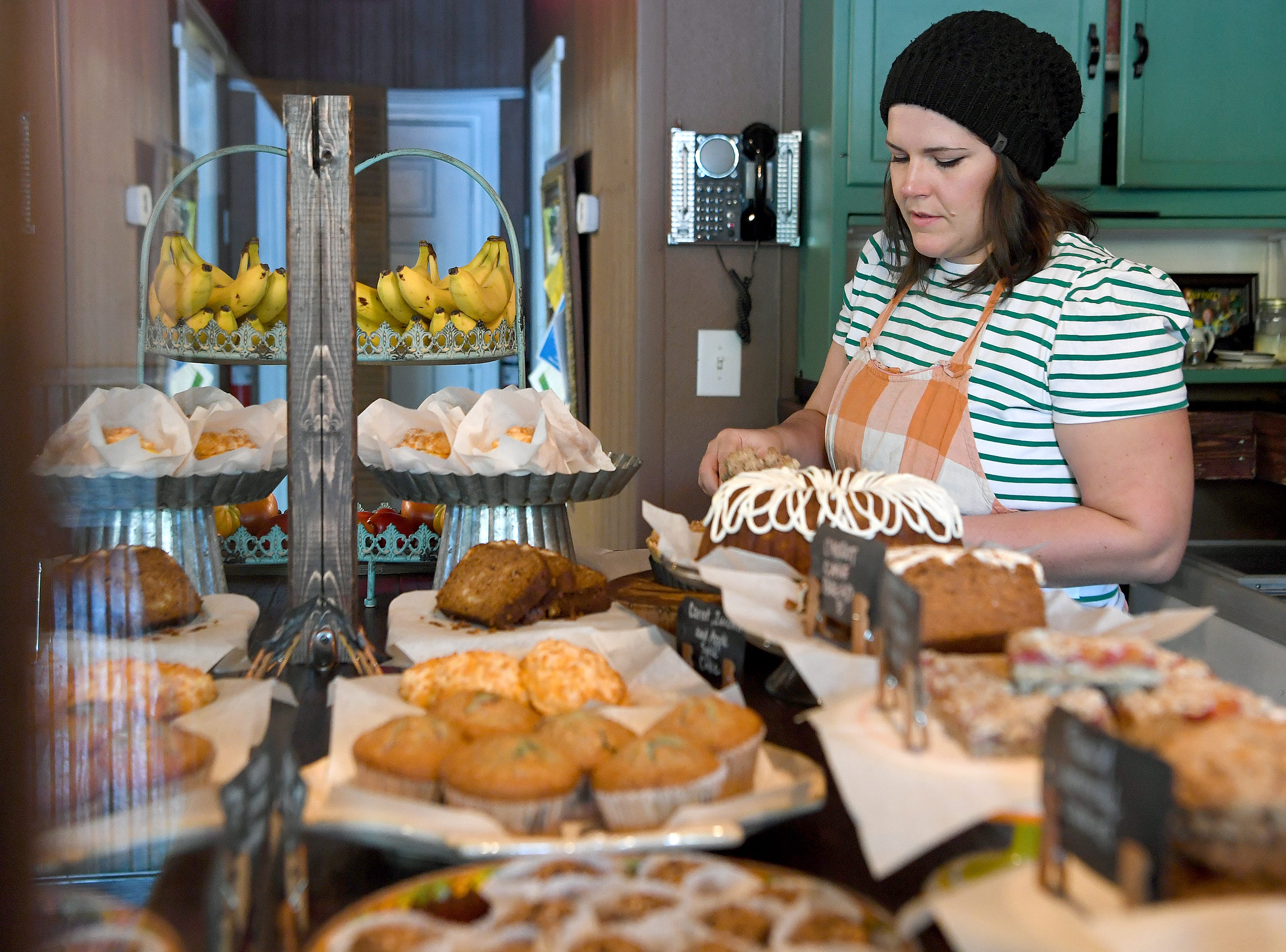 Barista Rachael Petty cuts a slice of cake for a customer at the Beehive Coffee Bar in Arden on Sept. 19, 2018. She bakes the shop's offerings fresh daily.