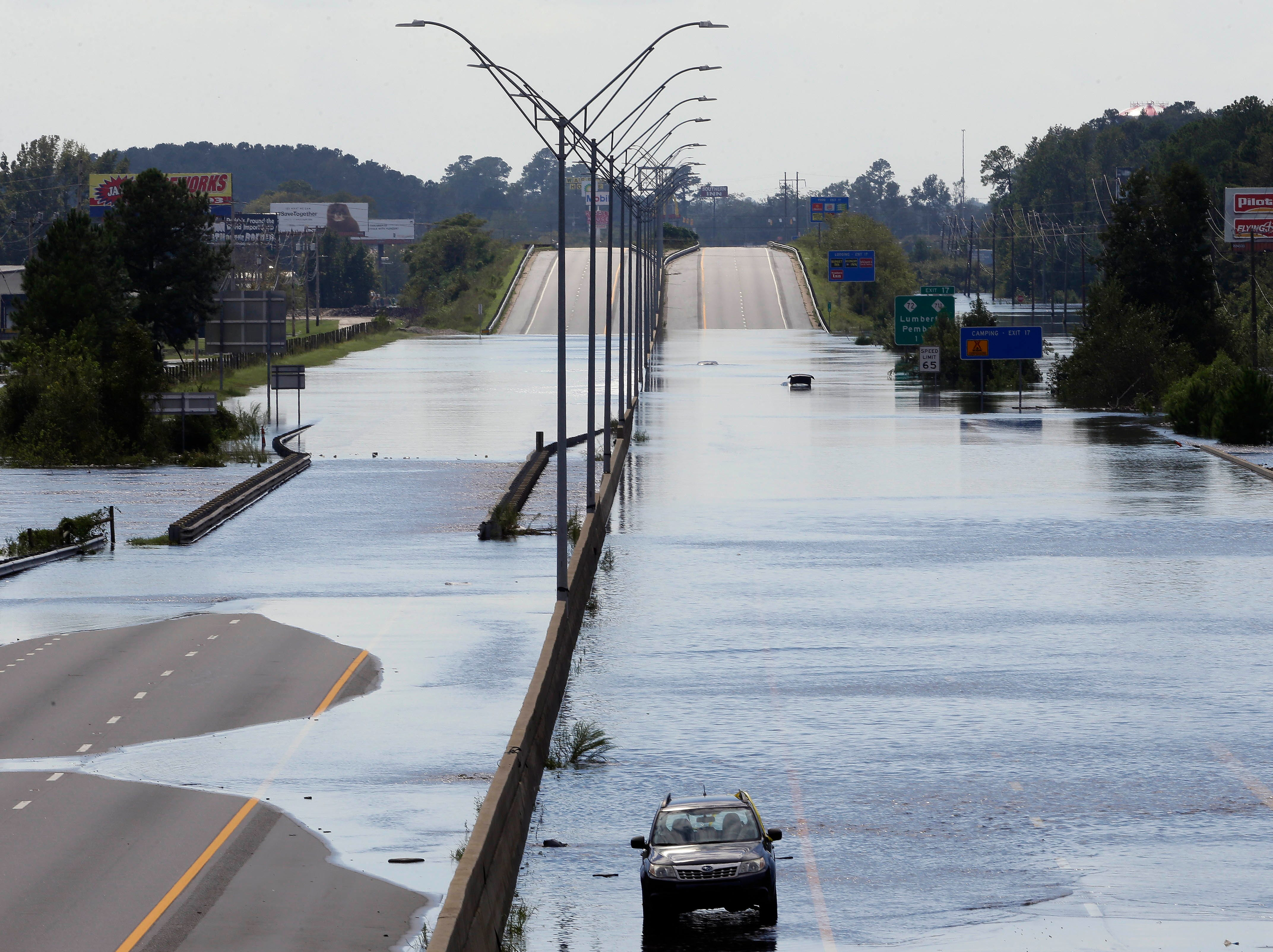 In this Sept. 17 photo, flooded vehicles sit on a closed section of Interstate 95 in Lumberton, where the Lumber river overflowed following flooding from Hurricane Florence.