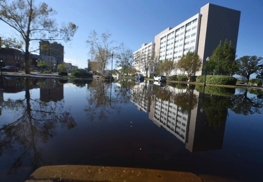 The Hotel Ballast is reflected in floodwaters from the Cape Fear River along Water St. in downtown Wilmington Sunday. The river is expected to crest on Monday night.
