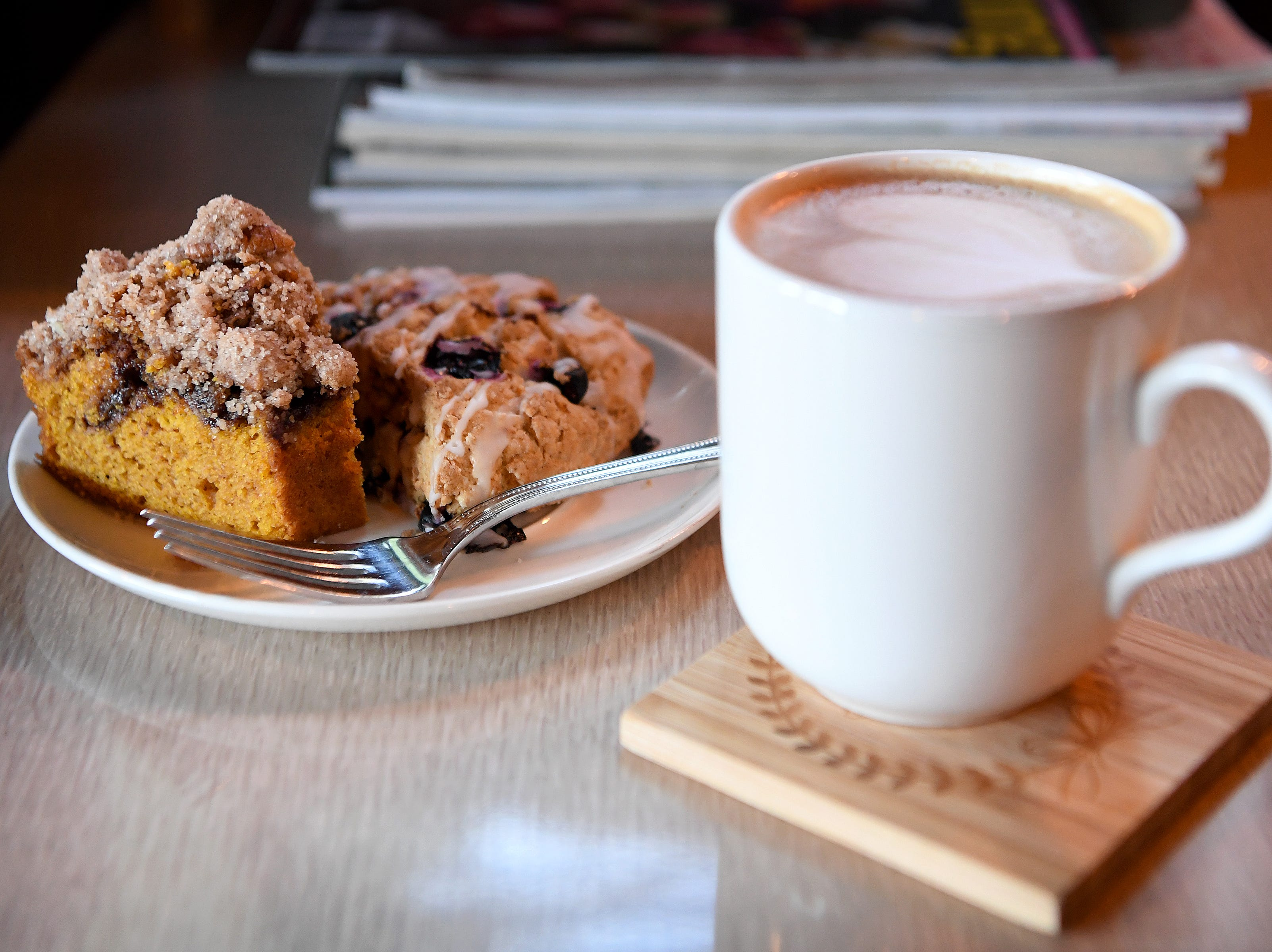 A latte is accompanied by house-made pumpkin chocolate chip coffee cake and a vegan scone at the Beehive Coffee Bar in Arden.