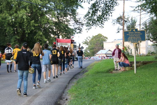 Members of the Otselic Valley Central School Band march on Route 26 in front of the Valley View cemetery and the Grace Brown historical marker.