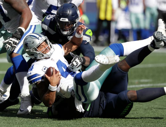 Dallas Cowboys quarterback Dak Prescott (4) is sacked by Seattle Seahawks defensive end Dion Jordan (top) and defensive tackle Jarran Reed.