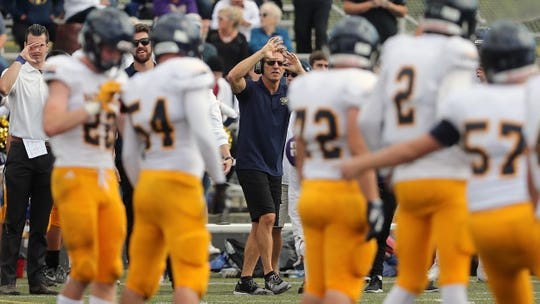 Bainbridge football coach Jeff Rouser gives a signal to his offense from the sidelines during their game against North Kitsap on September 1, 2018.