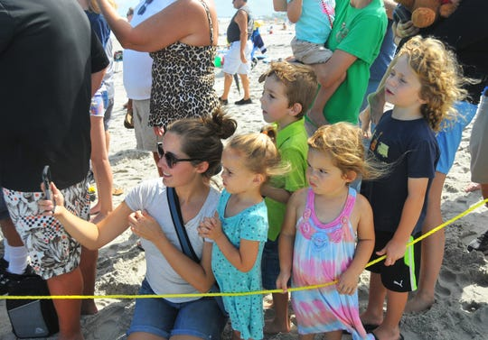 Kayli Ciambotti, surrounded by children, watches Guacamole make her way into the ocean Monday at Lori Wilson Park in Cocoa Beach.