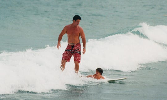 In this 2006 photo provided by the Marks family, Caroline Marks surfs for the first time at age 4 with her father, Darren Marks, in Melbourne Beach.