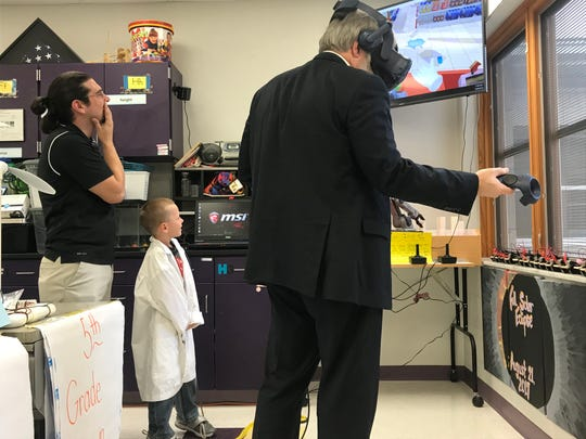 State Superintendent of Public Instruction Paola DeMaria tries out a virtual reality program being used by Unioto Elementary's SCOPES program in which the user is a store clerk helping visitors stock up in preparation for an approaching hurricane.