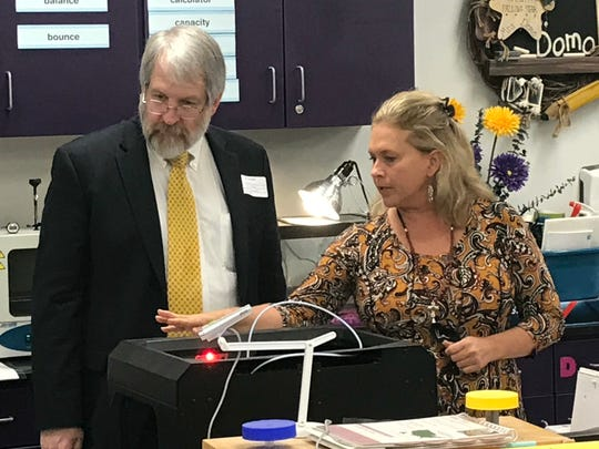 Unioto Elementary SCOPES teacher Jenni Domo explains to State Superintendent of Public Education Paolo DeMaria how the program's 3-D printer is being used in a hurricane-related project the students are doing.
