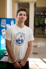 Spenser Brown, Ohio University Interfraternity Council vice president of public relations, stands in the Baker Center at Ohio University asking students to pose with statements against sexual assault to post on social media.