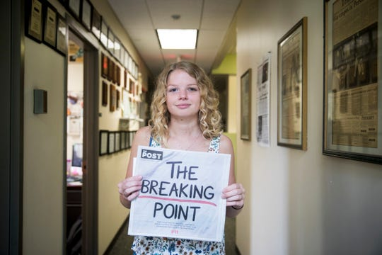 "Ellen Wagner, news editor of the student-run newspaper, The Post, holds her article, ""Enough is Enough"" about the campus response to the reports of sexual assaults."