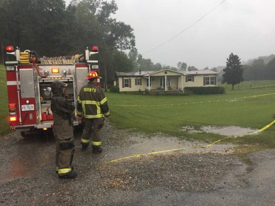 First responders stand near the home in Indian Mound where officials say Brenda Smith was killed after someone broke in and set a fire.