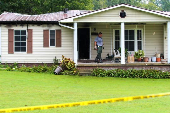 An investigator on Monday, Sept. 24, looks over the scene at Rorie Hollow Road in Indian Mound, where a woman was killed in a home invasion arson on Sunday.