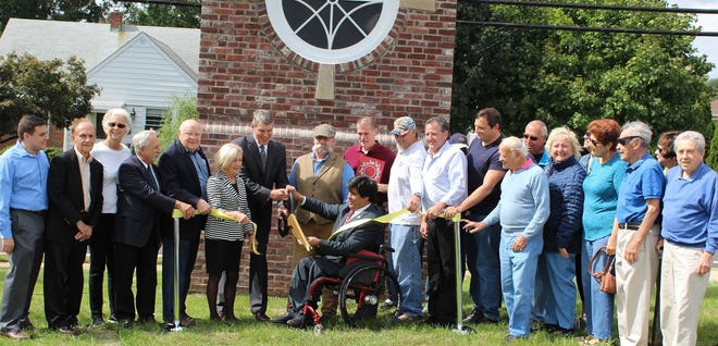Freeholder Director Patrick Scaglione and Raritan Mayor Chuck McMullin are joined by Freeholder Patricia Walsh in cutting the ribbon to dedicate the Washington School monument on First Avenue in Raritan. Former teachers, former students and former Principal Wilson Bethard also were part of the ceremony.