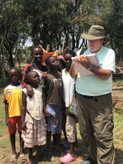 Brother Mickey McGrath, OSFS, posed with young people during a recent sketching tour of Kenya