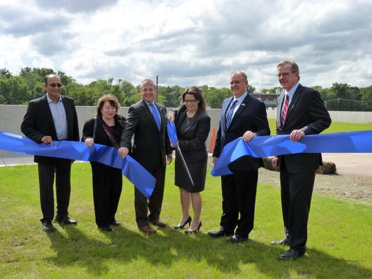 New Jersey American Water President Deborah Degillio, with scissors, cutting the ribbon on a new flood protection project. She's joined by Somerset County Business Partnership President Michael Kerwin, right, New Jersey American Water Senior Director Bob Schaefer, David Zimmer, the executive director of the New Jersey Environmental Infrastructure Trust, and Manoj Patel, project manager.