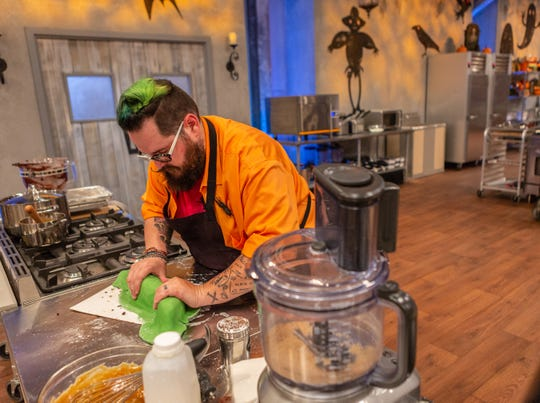 Contestant Andrew Fuller rolls fondant on to his dish for the pre-heat challenge, as seen on Food Network's Halloween Baking Championship Season 4.