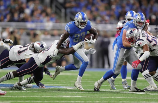 Detroit Lions running back Kerryon Johnson runs the ball behind guard Frank Ragnow against the New England Patriots during the first quarter Sunday, Sept. 23, 2018 at Ford Field.