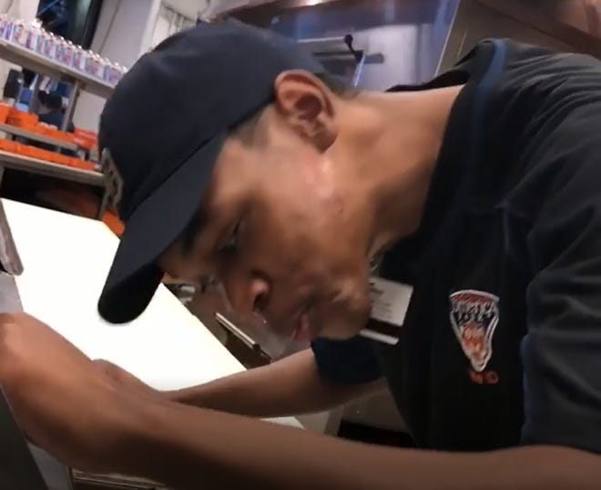 A screenshot from a video in which a Comerica Park employee spits on a pizza on September 21, 2018.