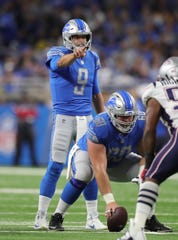 Matthew Stafford runs the offense with center Graham Glasgow during the first quarter Sunday.