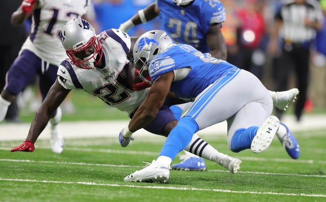 Detroit Lions safety Glover Quin tackles New England Patriots running back Sony Michel during the first quarter Sunday, Sept. 23, 2018 at Ford Field.