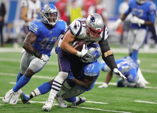 Detroit Lions defenders Jarrad Davis (40) and Glover Quin (27) tackle New England Patriots tight end Rob Gronkowski during the second half Sunday, Sept. 23, 2018 at Ford Field.