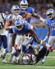 Detroit Lions running back Kerryon Johnson runs the ball against the New England Patriots during the first quarter Sunday, Sept. 23, 2018 at Ford Field.