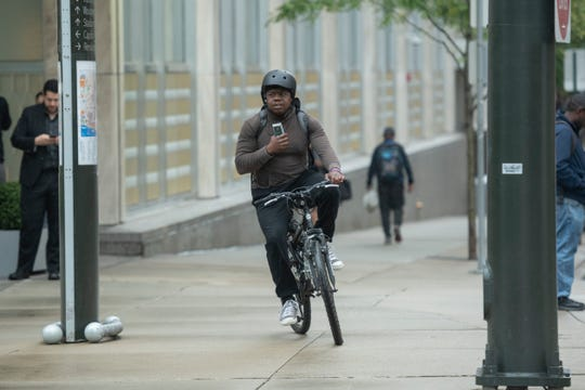 Danny Butler III rides his bike from his job at Quicken Loans to his home in the New Center area after work.