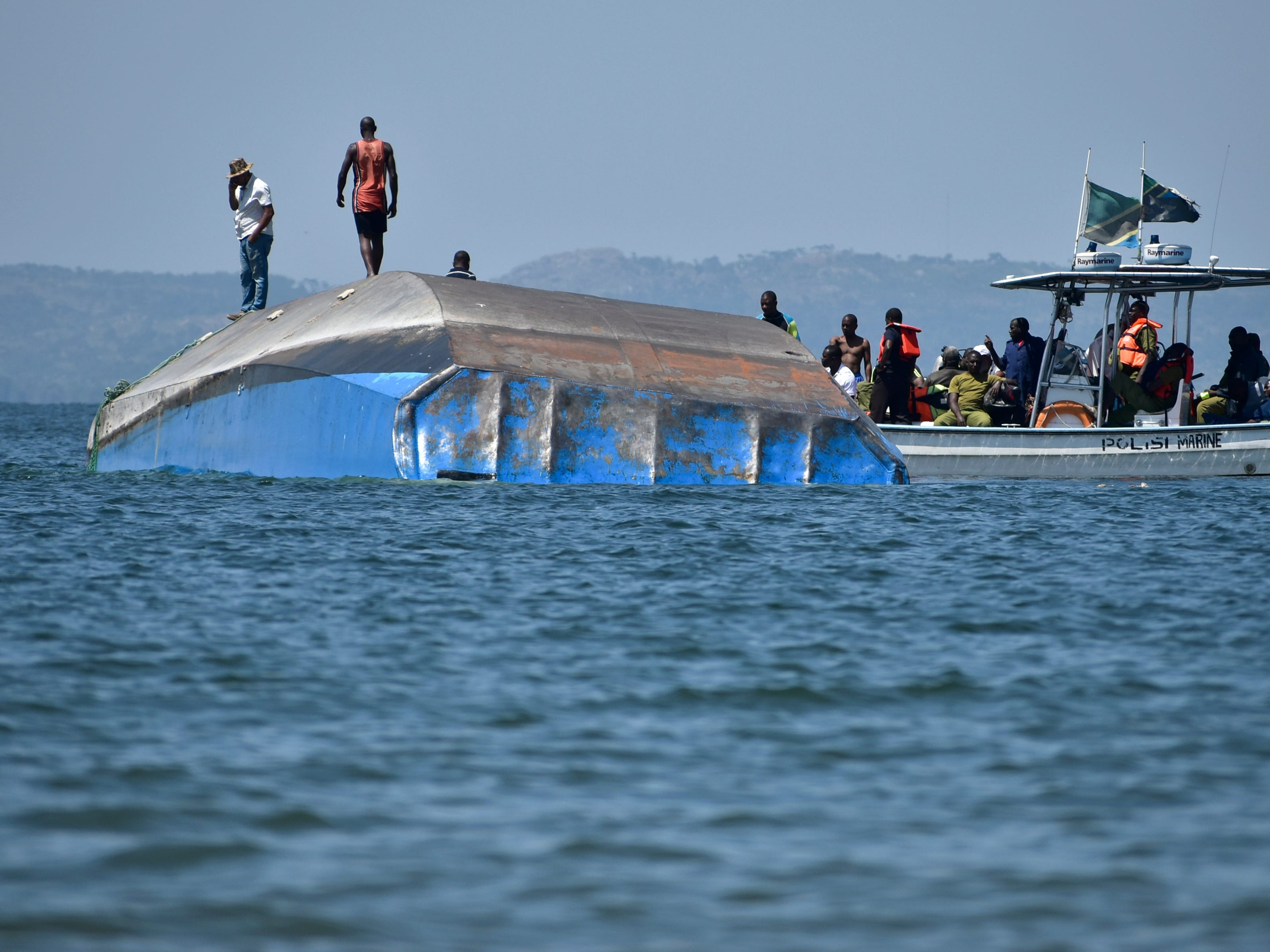 Rescue workers observe the capsized MV Nyerere passenger ferry as it lies upturned near Ukara Island, Tanzania Sunday, Sept. 23, 2018. Burials started Sunday of the more than 200 people who died when the ferry capsized on Lake Victoria, while the country's Defense Minister said no further survivors were likely to be found and search efforts had ended.