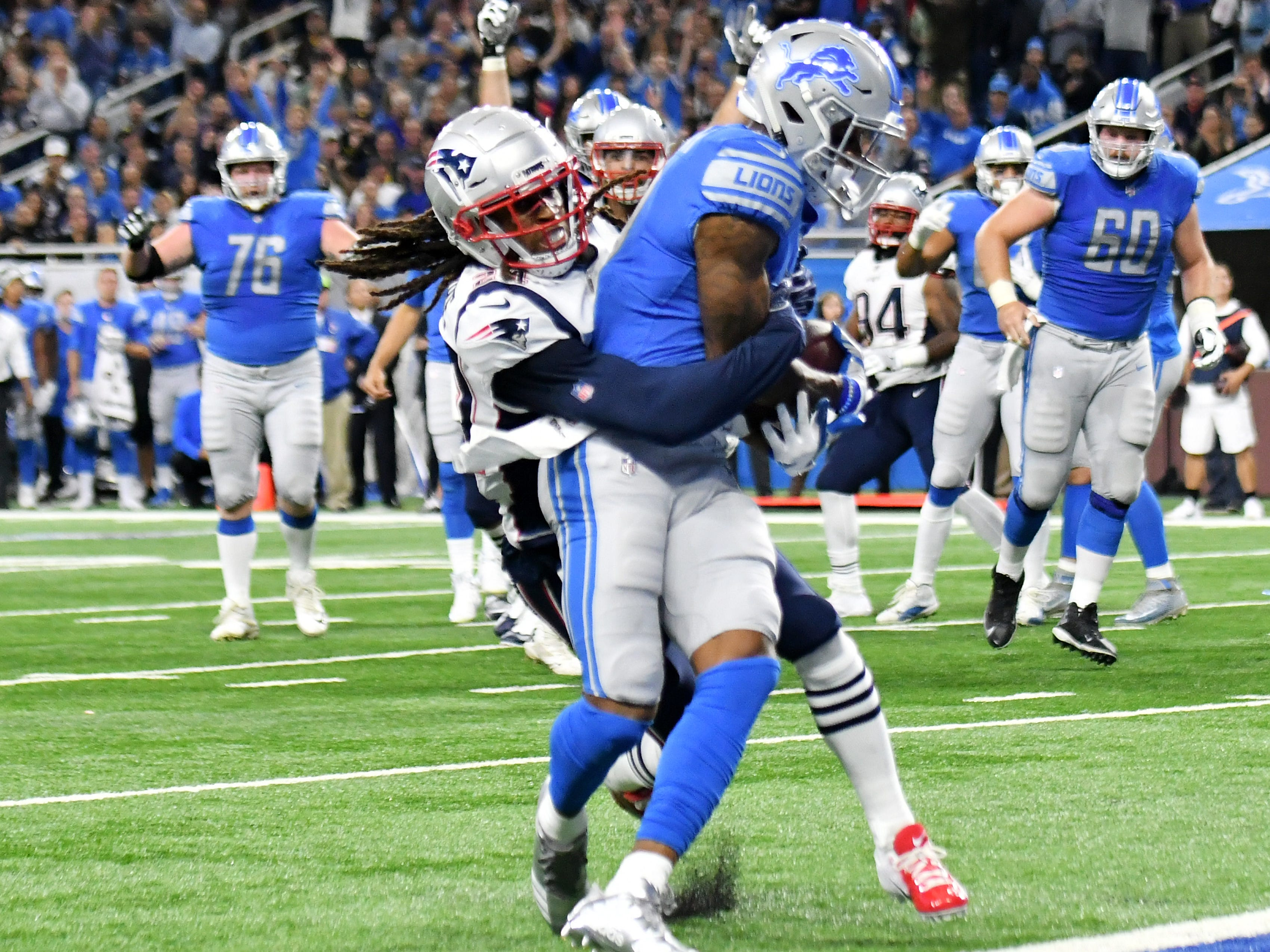 The Patriots' Stephon Gilmore, left, tries to tackle the Lions' Kenny Golladay at the goal line in the second quarter. The play was ruled short initially but after a challenge and review it was ruled a touchdown.