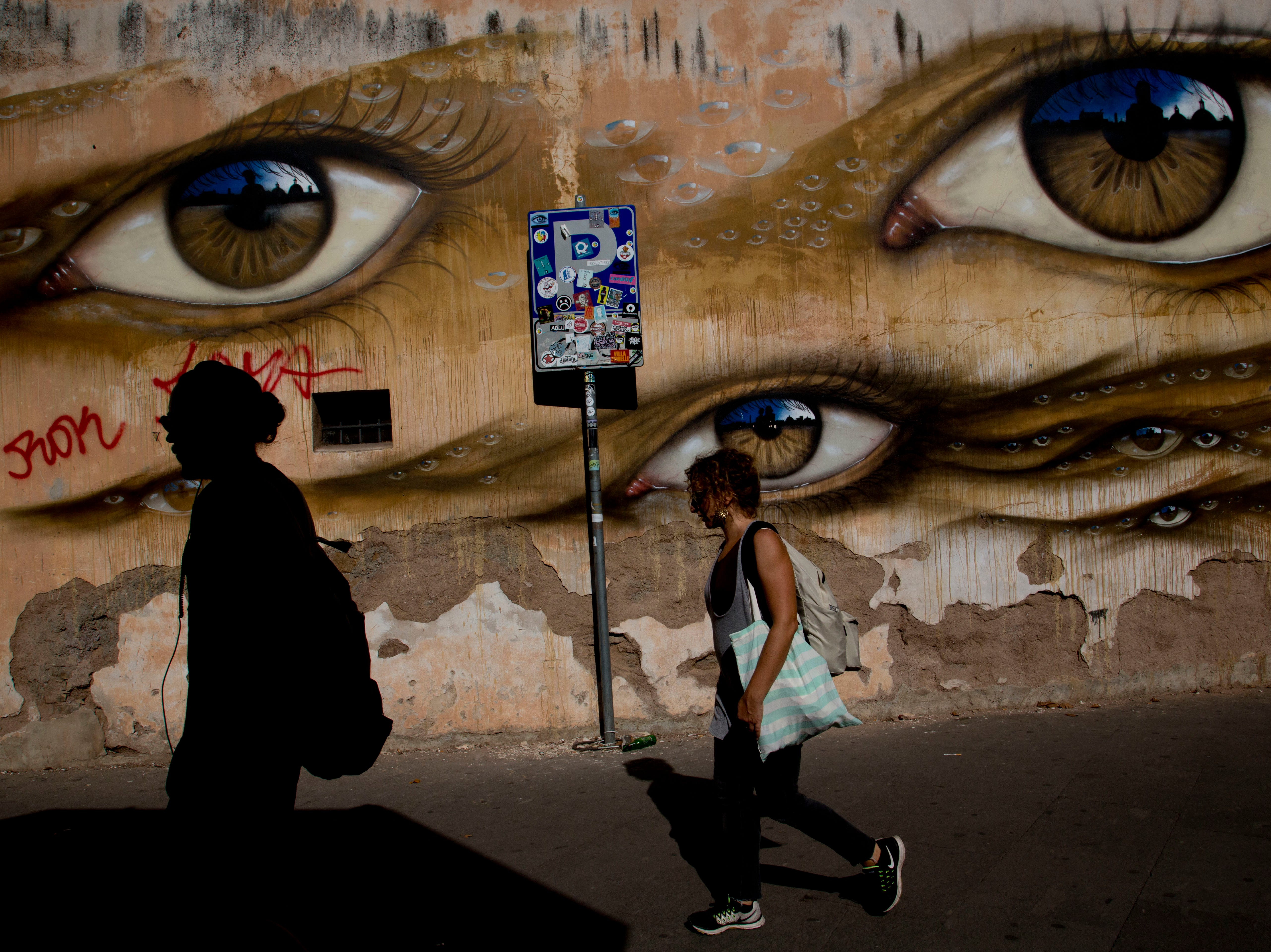 People walk past the mural by British street artist My Dog Sighs, in Rome's Trastevere neighborhood, Monday, Sept. 24, 2018.