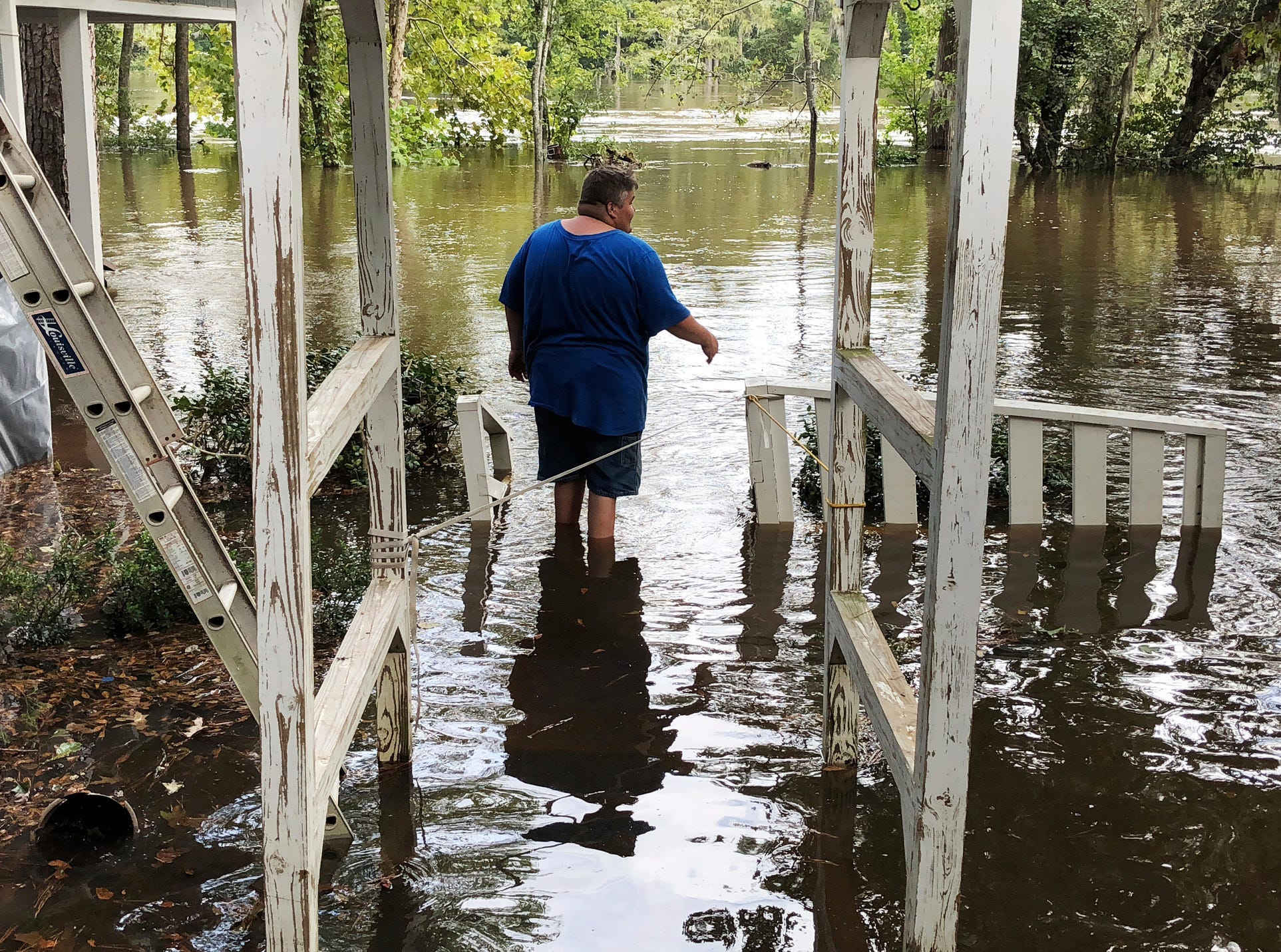 Shawn Lowrimore, Pastor Willie Lowrimore of The Fellowship With Jesus Ministries', son, wades into water near the church in Yauhannah, S.C., on Monday, Sept. 24, 2018. The church is on the bank of the Waccamaw River which has already risen above its record crest and is expected to keep rising for several days, forcing thousands of evacuations in the aftermath of Hurricane Florence.