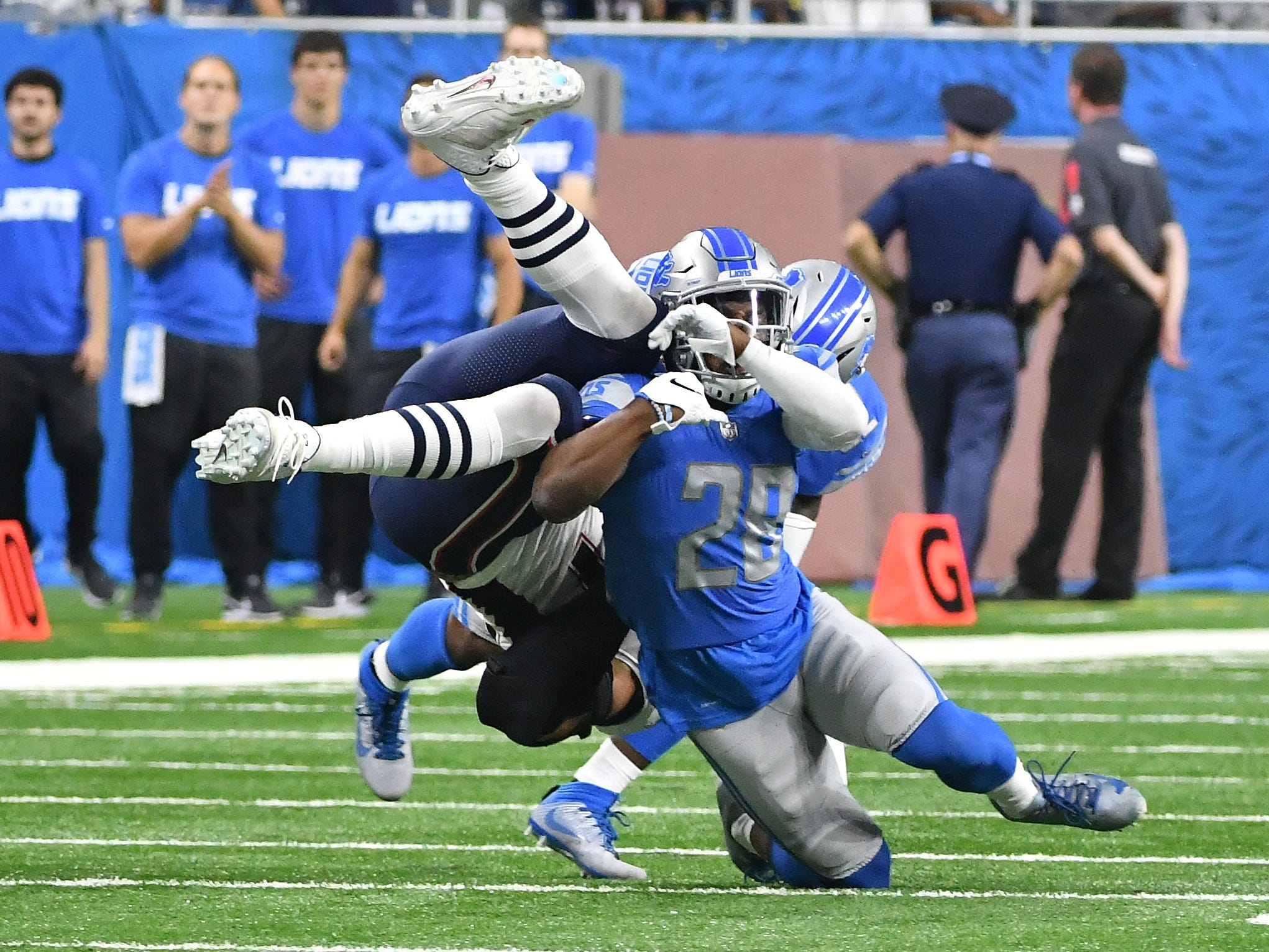 Lions' Quandre Diggs and Tavon Wilson brings down Patriots' Rob Gronkowski after a reception in the second quarter.