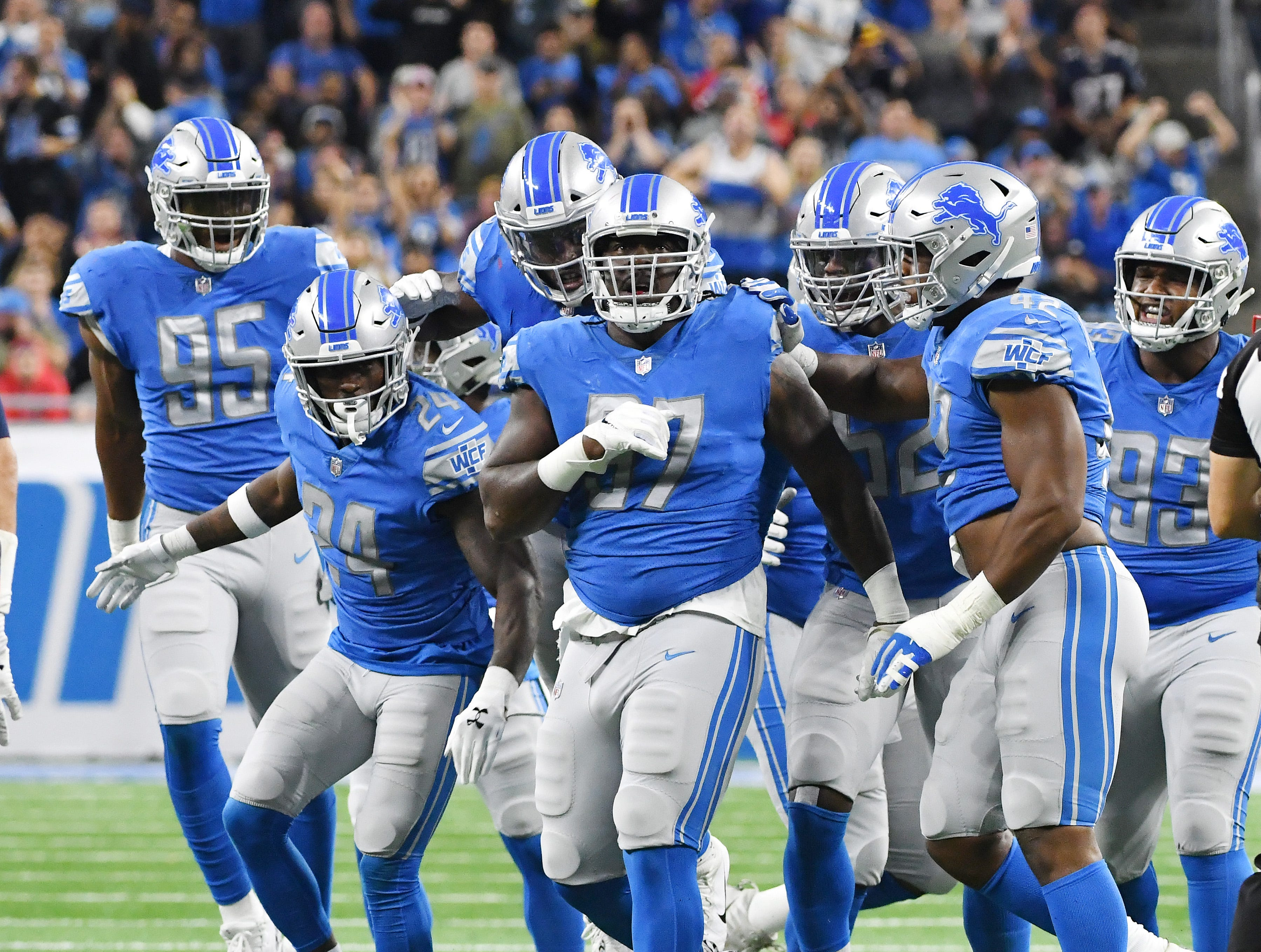 Lions celebrate with teammate Ricky Jean Francois after stopping the Patriots on third down forcing New England to punt in the second quarter.