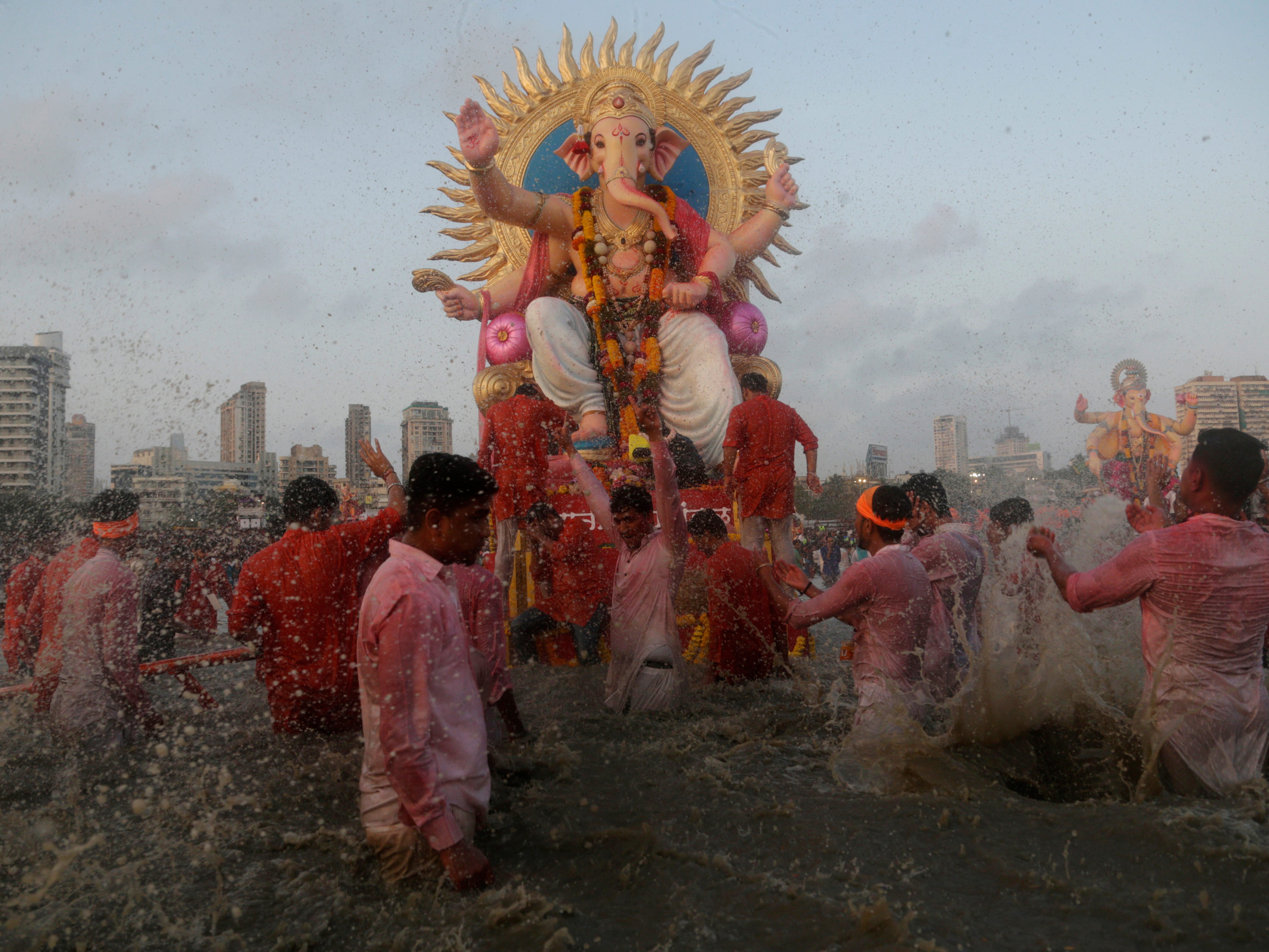 Devotees prepare to immerse idols of elephant-headed Hindu god Ganesha in the Arabian Sea, marking the end of the 10-day long Ganesh Chaturthi festival in Mumbai, India, Sunday, Sept. 23, 2018.