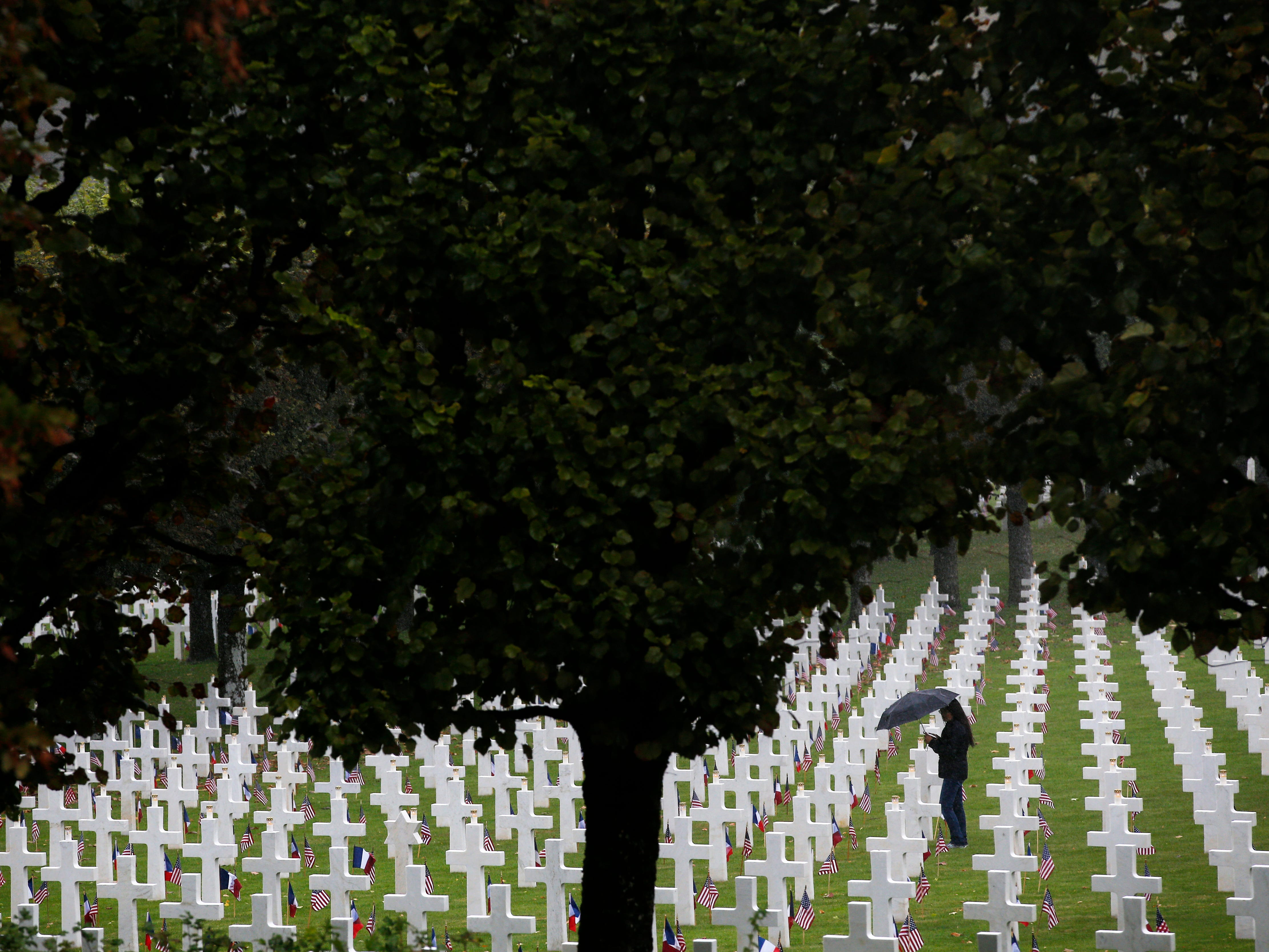 A woman walks in the Meuse-Argonne cemetery, northeastern France, during a remembrance ceremony, Sunday, Sept. 23, 2018. A remembrance ceremony is taking place Sunday for the 1918 Meuse-Argonne offensive, America's deadliest battle ever that cost 26,000 lives but helped bringing an end to World War 1.