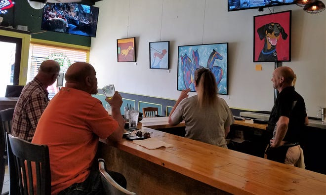 Mary Alicia Dennis and Scott Costin, on right, join customers in watching Sunday afternoon football at MaryScott's Kitchen.