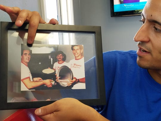 Francesco Bommarito points out his father Vito in a picture with his mother's brothers Tony and Joe at the first DiMaggio's Pizza in Fairfield, Ill.