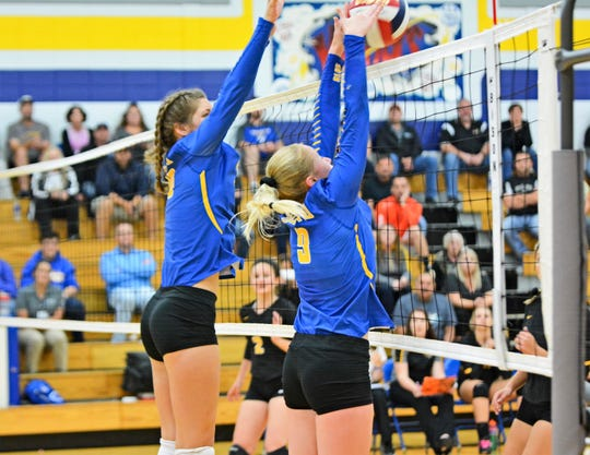 Hannah Moe and Emma Walkowiak successfully block an attack for a point for Oconto in their second game with Algoma on Sept. 20.