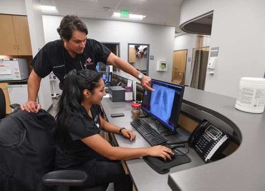 Dr. Jeff Harris looks over an x-ray with x-ray technician Olga Hernandez at American Family Care urgent care center in Duncan Monday, September 24 2018.