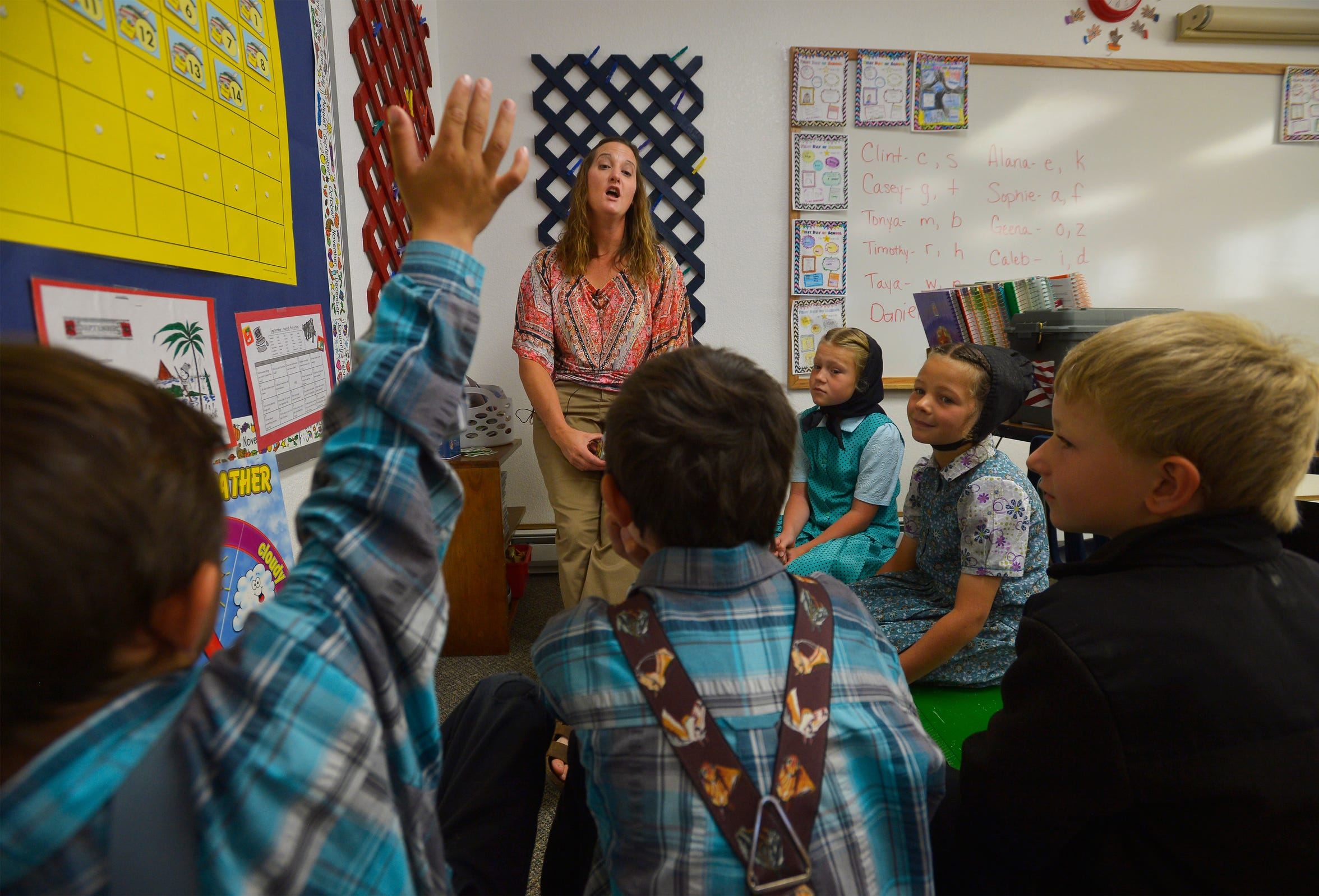 Traci Manseau leads her younger students in a lesson on days of the week.