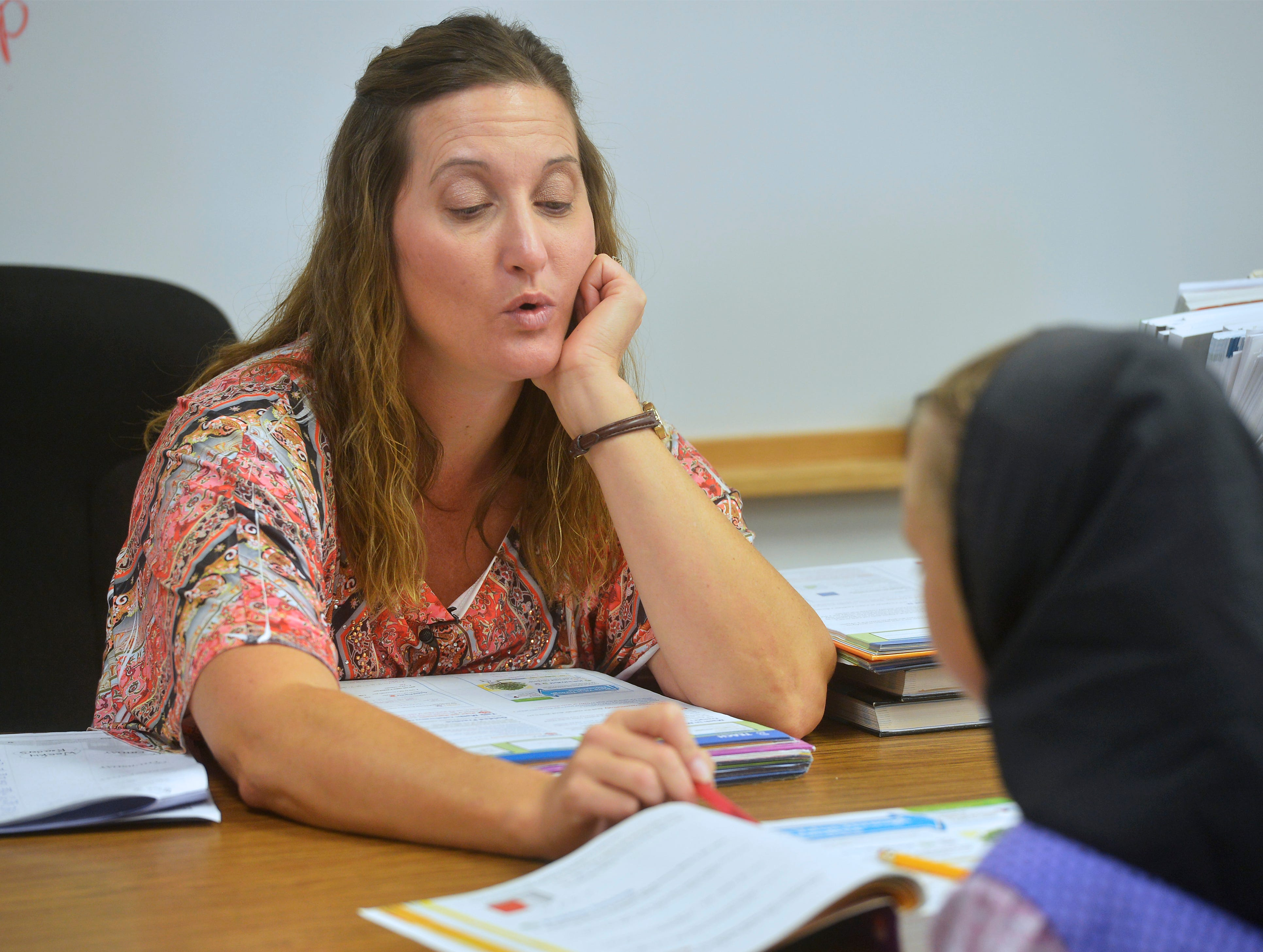 8:50 am:  Traci Manseau gives one on one instruction to one of her students, Monday, Sept. 17, 2018.  Monseau is a teaching veteran of 23 years and she has spent her entire career teaching in one room rural school houses.  She is currently teaching 15 students across seven different grade levels at the Deerfield Hutterite Colony in North Central Montana's Fergus County.