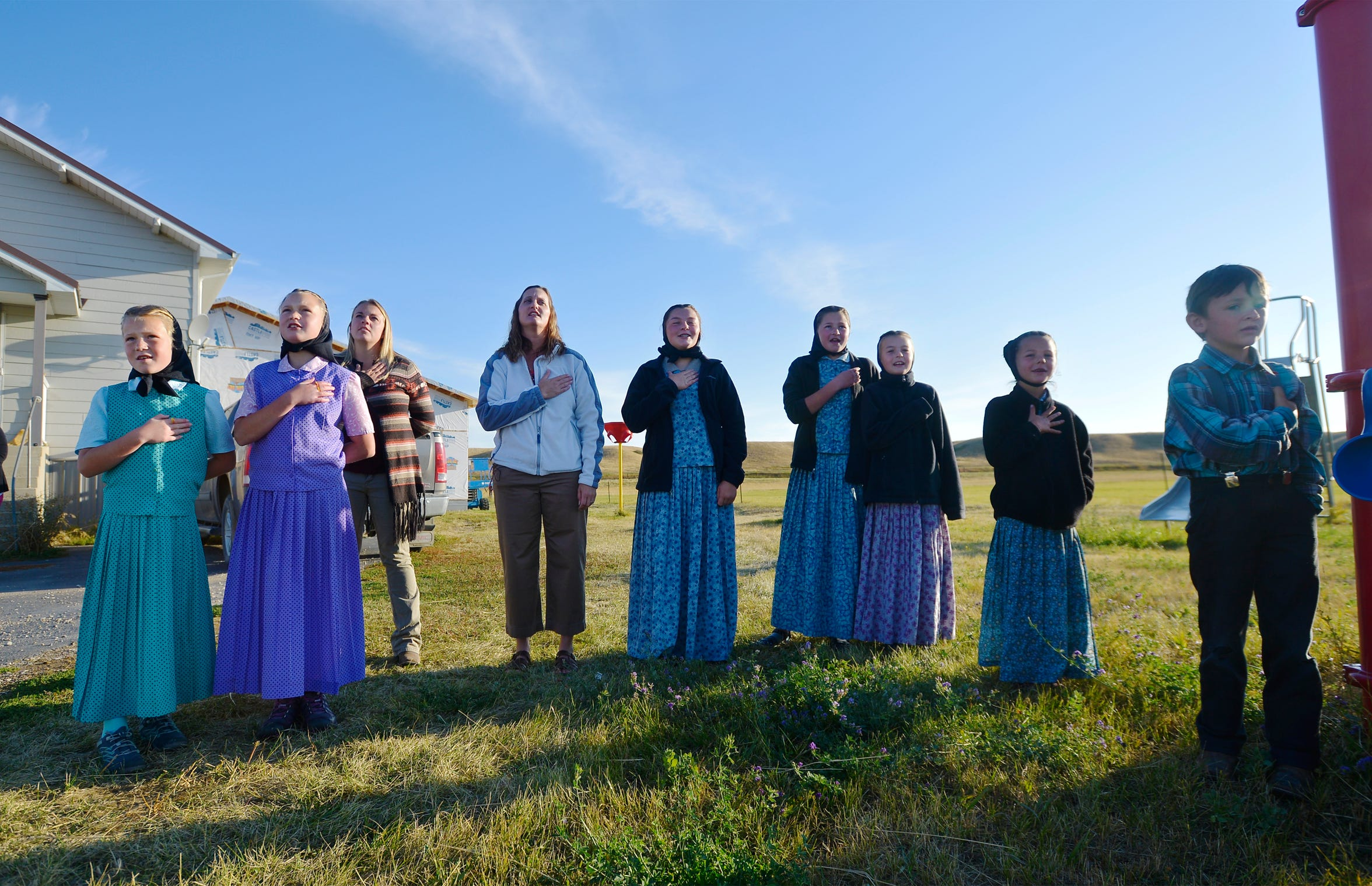 Deerfield School teacher Traci Manseau, her aide Kylee Clark and some of her students recite the Pledge of Allegiance around the flagpole. Older boys have to work in the Hutterite colony's dairy in the morning and come in late.