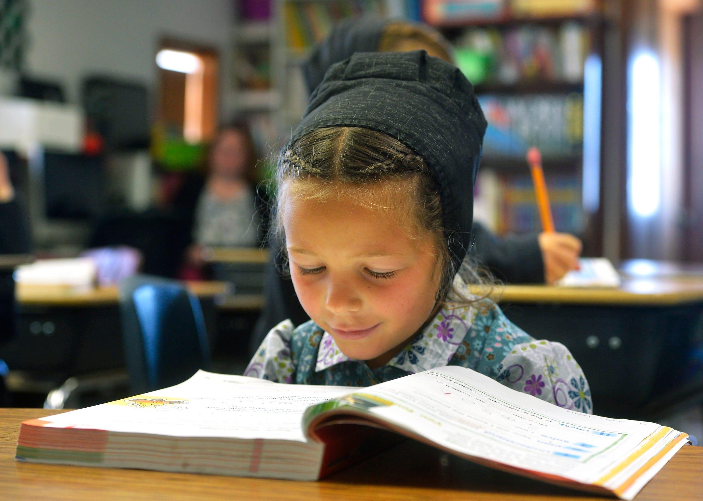 Amber Stahl reads at her desk at Deerfield School.