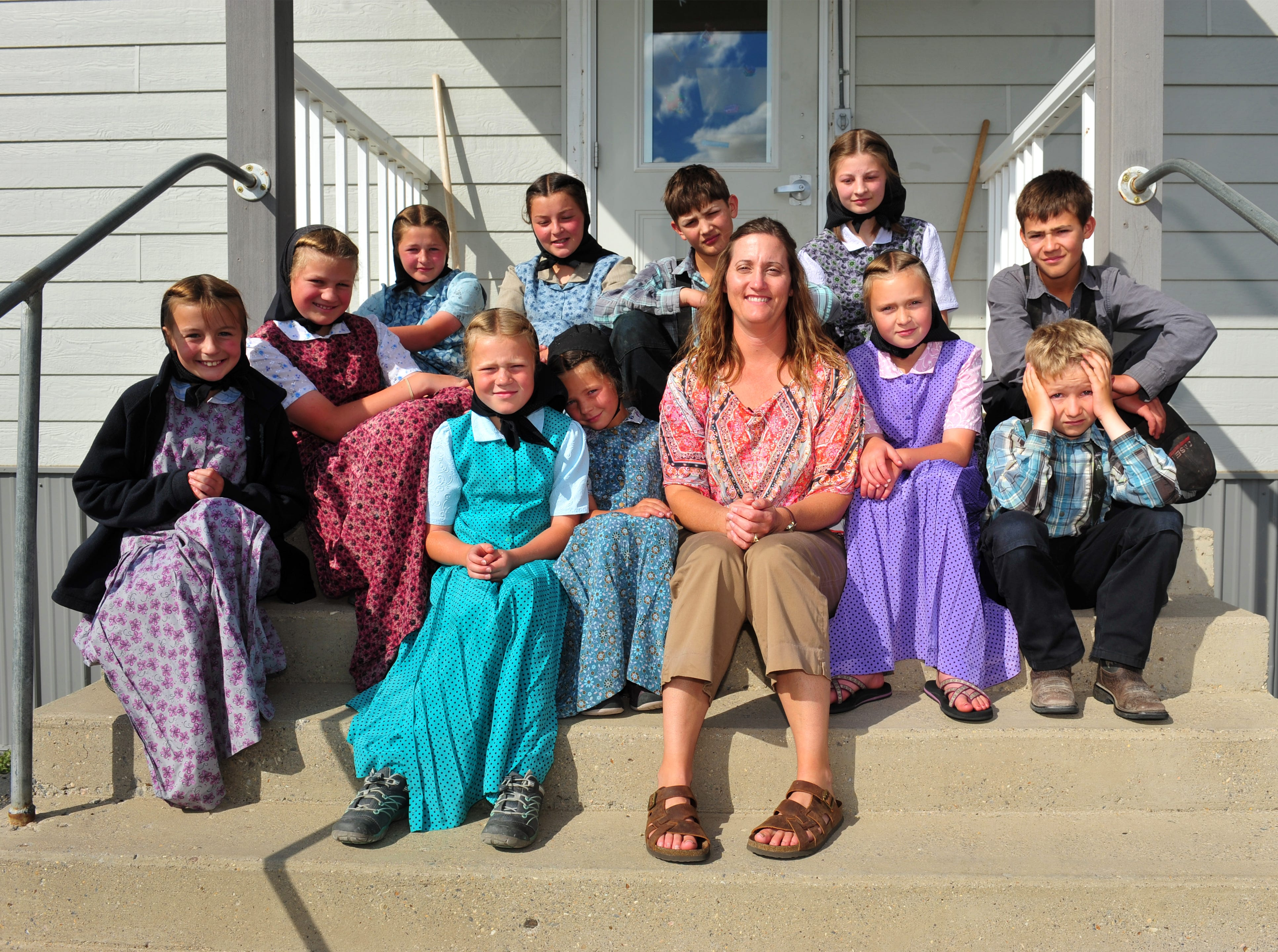 3:19 pm:  Traci Manseau sits with her class on the steps of their one room school house on the Deerfield Hutterite Colony, Monday, Sept. 17, 2018.  Manseau is a teaching veteran of 23 years and she has spent her entire career teaching in one room rural school houses.  She is currently teaching 15 students across seven different grade levels at the Deerfield Hutterite Colony in North Central Montana's Fergus County.